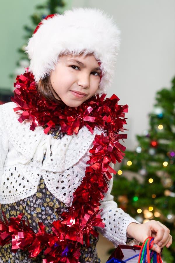 Menina caucasiano do preteen atrativo no chapéu de Santa e no ouropel, retrato, olhando a câmera imagem de stock royalty free
