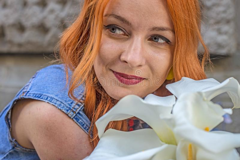Menina caucasiano do ruivo bonito que cheira flores coloridas no jardim foto de stock