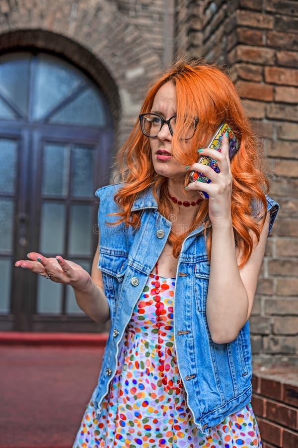 Menina caucasiano do ruivo confuso que fala no telefone esperto fotos de stock