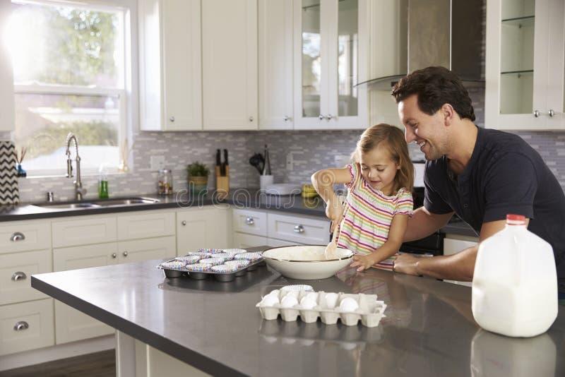 Menina caucasiano e paizinho que cozem junto na cozinha foto de stock