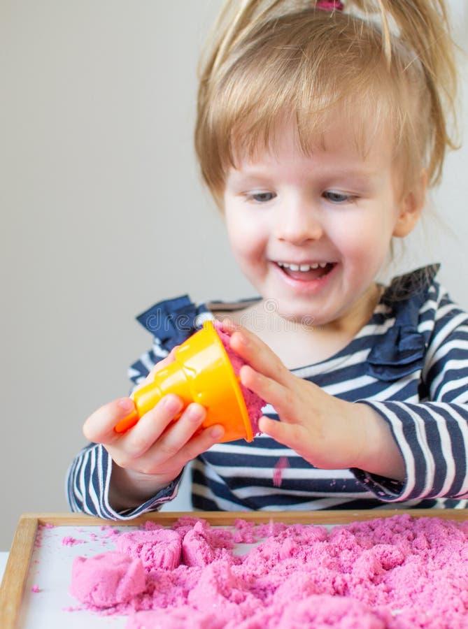 Menina caucasiano feliz pequena que joga com a areia cinética cor-de-rosa em casa fotografia de stock royalty free