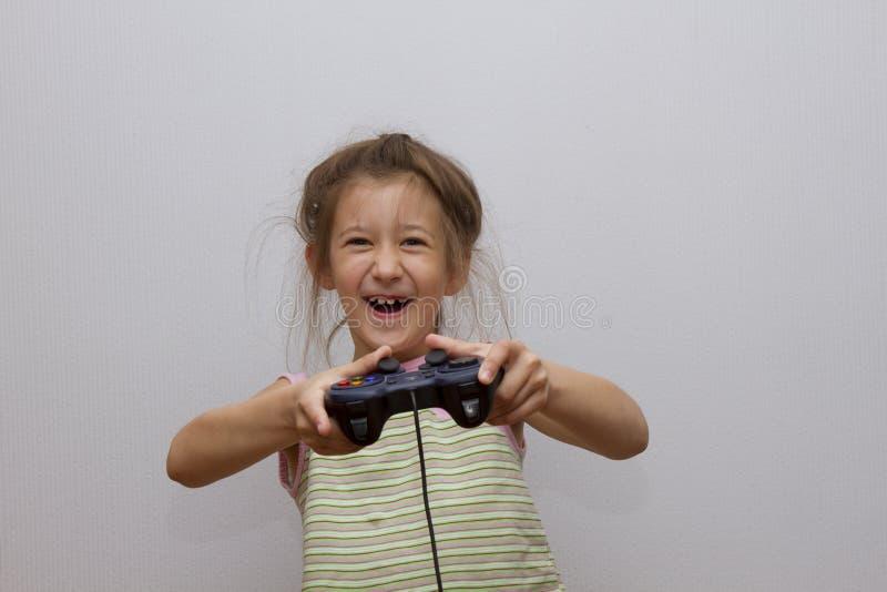 Menina caucasiano feliz que joga os jogos de vídeo que guardam o controlador do jogo fotos de stock