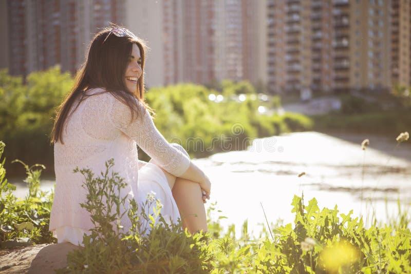 Menina caucasiano moreno bonita nova no vestido branco que senta o fotografia de stock royalty free