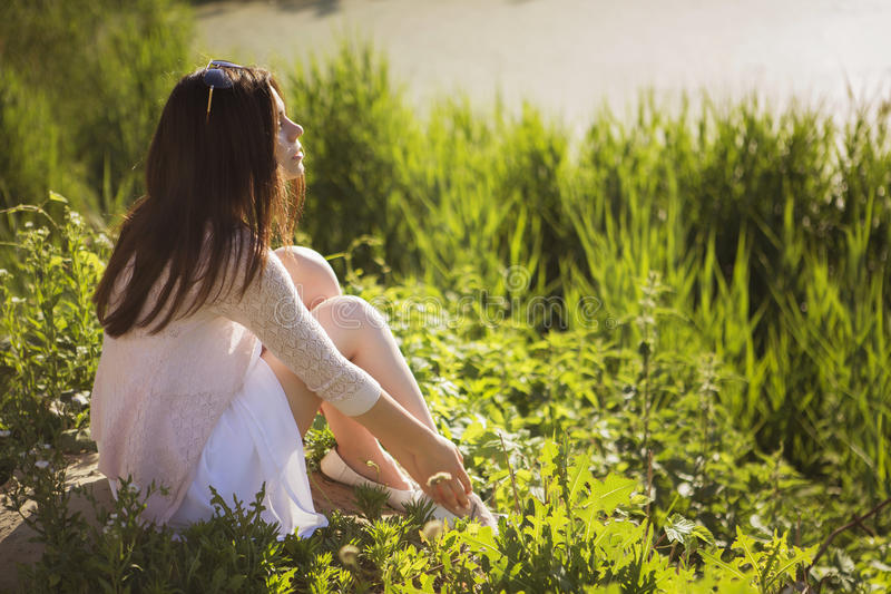 Menina caucasiano moreno bonita nova no vestido branco que senta o imagens de stock