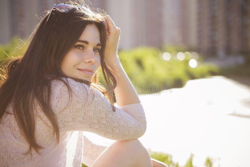 Menina caucasiano moreno bonita nova no vestido branco que senta o imagens de stock royalty free