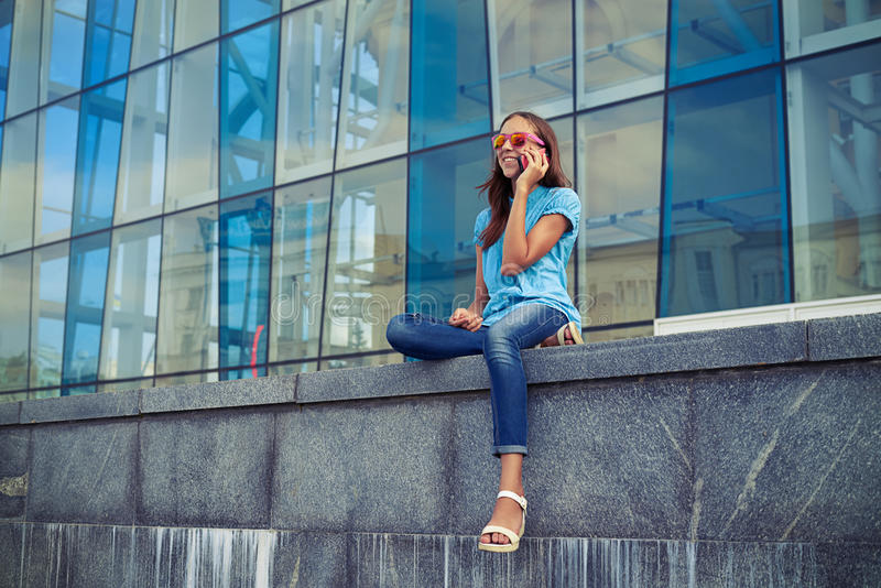 A menina caucasiano no humor alegre falar no telefone esperto quando fotos de stock royalty free