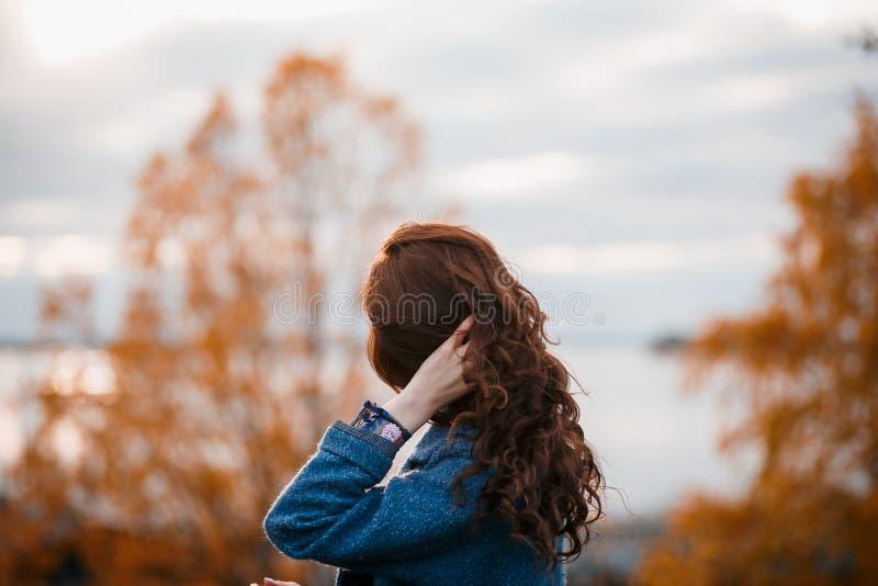 Menina caucasiano nova bonita do cabelo encaracolado que veste fora o revestimento azul, levantando no parque do outono fotos de stock royalty free