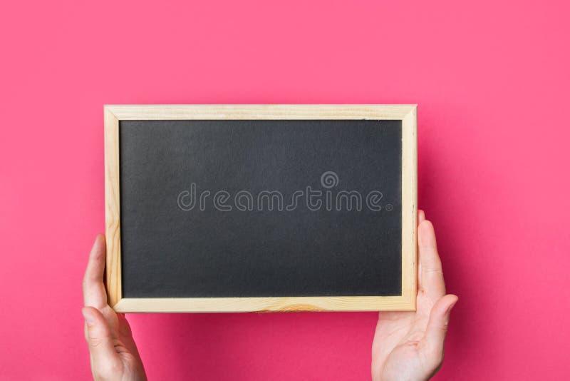 A menina caucasiano nova da mulher realiza no quadro preto vazio das mãos no fundo cor-de-rosa fúcsia vibrante De volta ao concei foto de stock