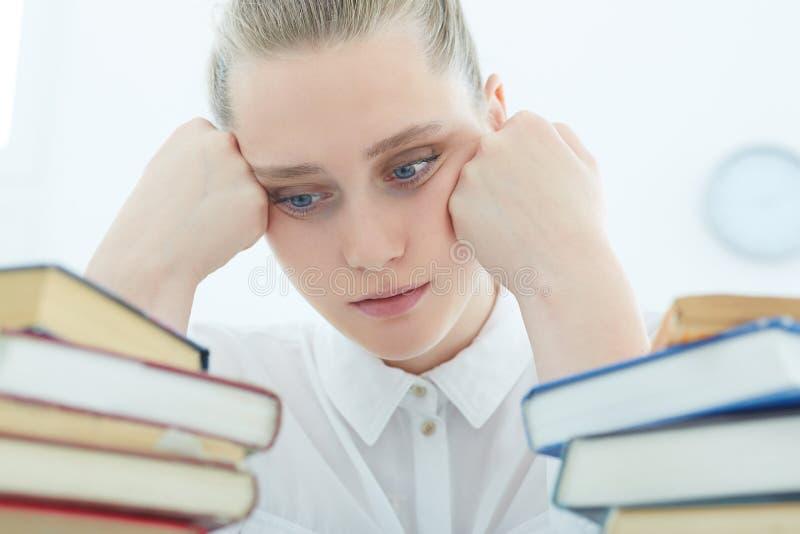 Menina caucasiano pensativa do estudante cansado olhando as pilhas de livros foto de stock