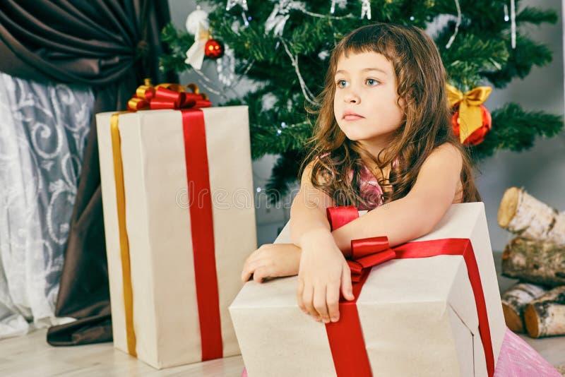 Menina caucasiano pequena bonito pensativa da criança com a árvore de Natal próxima atual dentro foto de stock