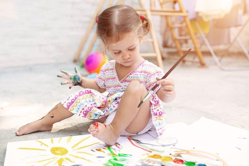 Menina caucasiano pequena bonito que aprecia a pintura no quintal com papel, cor de água e escova da arte Foco seletivo fotos de stock royalty free