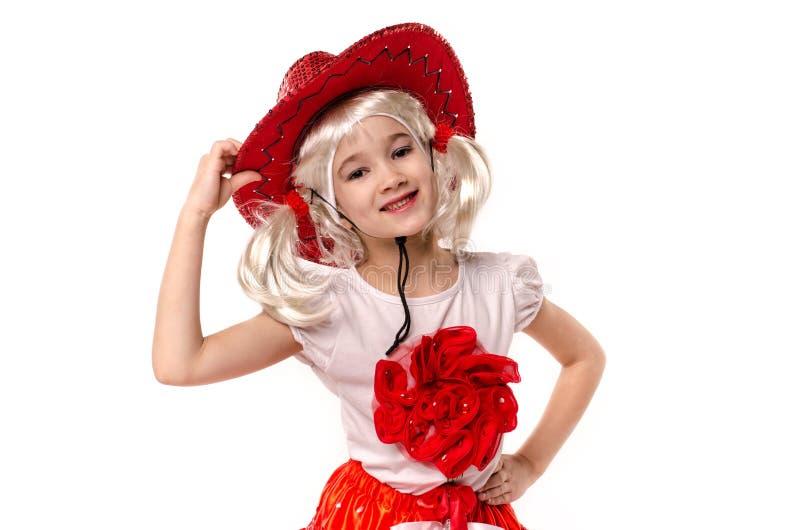 Menina caucasiano pequena bonito que veste a saia vermelha, o t-shirt com flores e o chapéu de vaqueiro isolado no fundo branco fotografia de stock royalty free