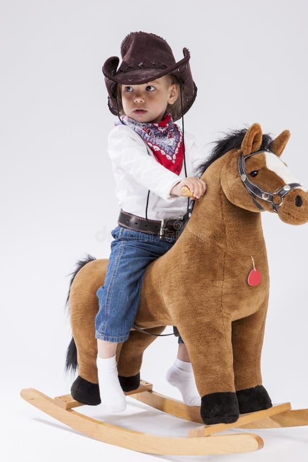 Menina caucasiano pequena calma assegurada na roupa da vaqueira no cavalo simbólico contra o fundo branco fotos de stock royalty free
