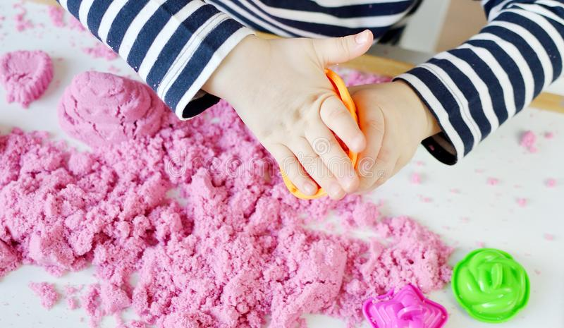 Menina caucasiano pequena que joga com a areia cinética cor-de-rosa em casa imagens de stock