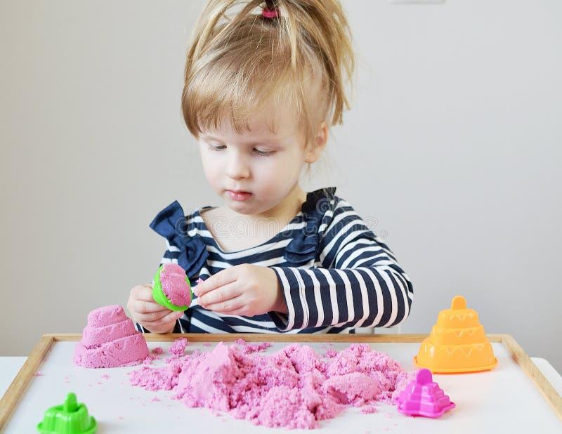 Menina caucasiano pequena que joga com a areia cinética cor-de-rosa em casa imagem de stock royalty free
