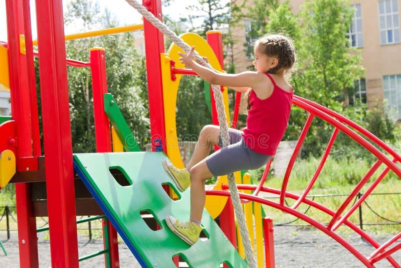 Menina caucasiano pequena que joga no campo de jogos, escalando a parede em uma corda foto de stock