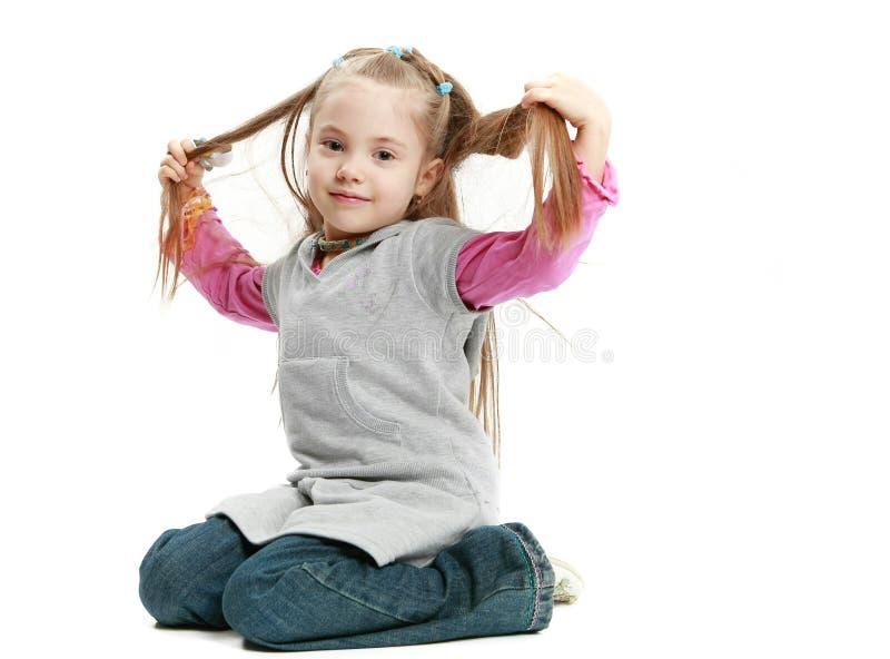 A menina caucasiano pequena senta e toca em seu cabelo no wh fotografia de stock