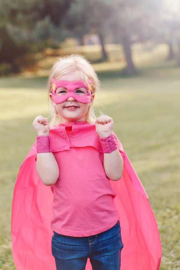 Menina caucasiano pré-escolar da criança que joga o super-herói foto de stock