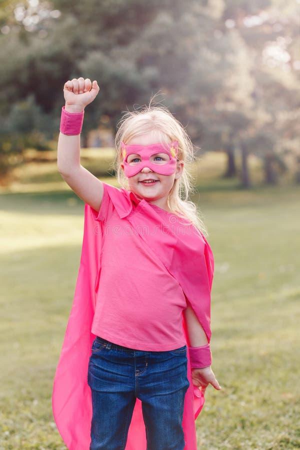 Menina caucasiano pré-escolar da criança que joga o super-herói imagens de stock royalty free
