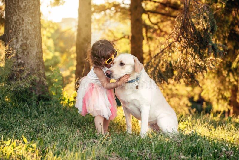 Menina caucasiano que abraça beijando seu cão no parque foto de stock royalty free