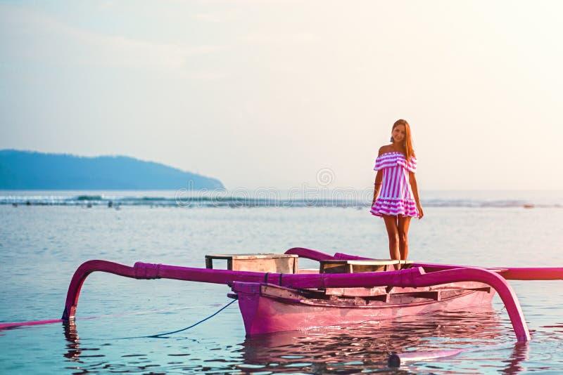 Menina caucasiano que levanta a posição em um barco cor-de-rosa no mar no por do sol na ilha de Gili fotos de stock