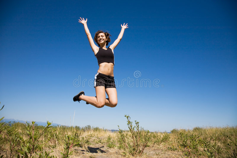 Menina caucasiano que salta para a alegria fotos de stock royalty free
