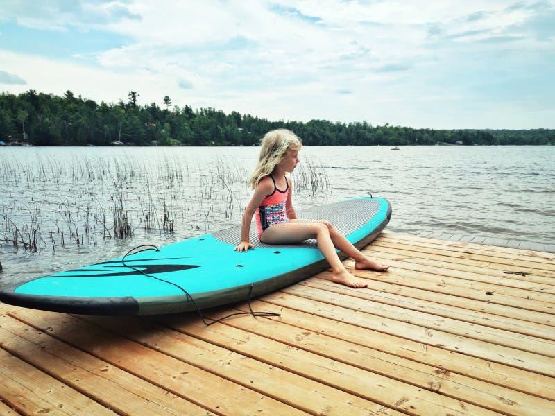 Menina caucasiano que senta-se na placa de ressaca da pá pelo rio do lago imagens de stock royalty free