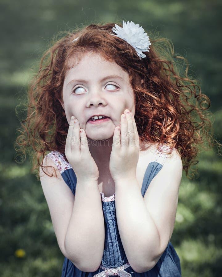 menina caucasiano ruivo no vestido azul que faz as caras parvas assustadores engraçadas fotos de stock royalty free