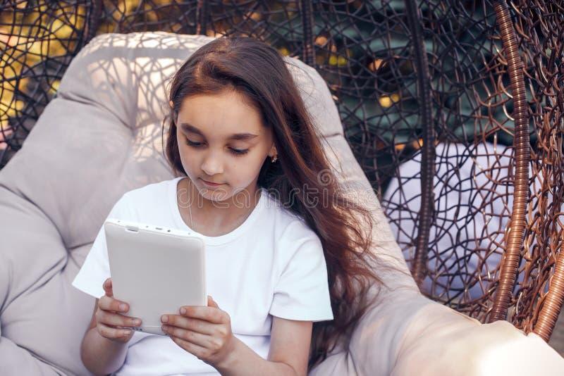 Menina caucasiano séria que usa o PC branco da tabuleta, sentando-se em um parque imagem de stock