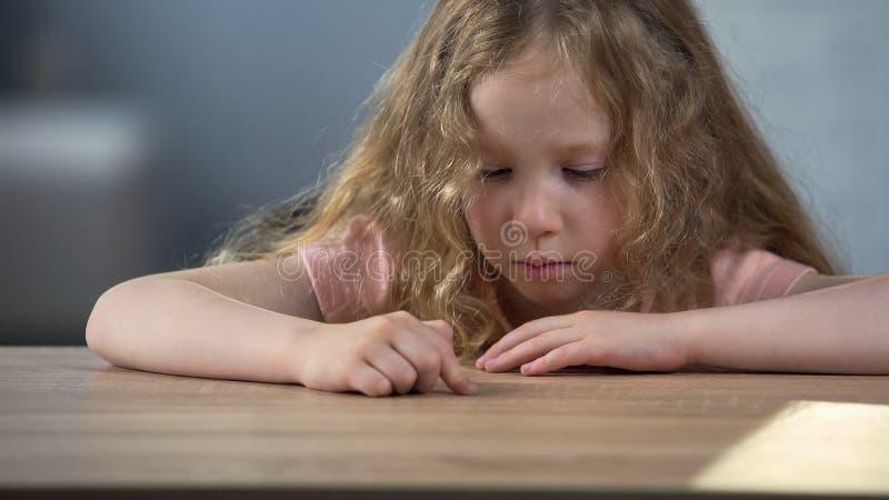 Menina caucasiano só que senta-se apenas na tabela e que sonha sobre a irmã mais nova foto de stock