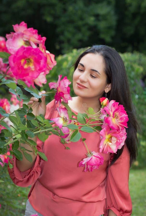 A menina cheira o sabor das rosas fotografia de stock
