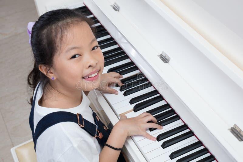 Menina chinesa asiática feliz que joga o piano clássico em casa imagens de stock royalty free