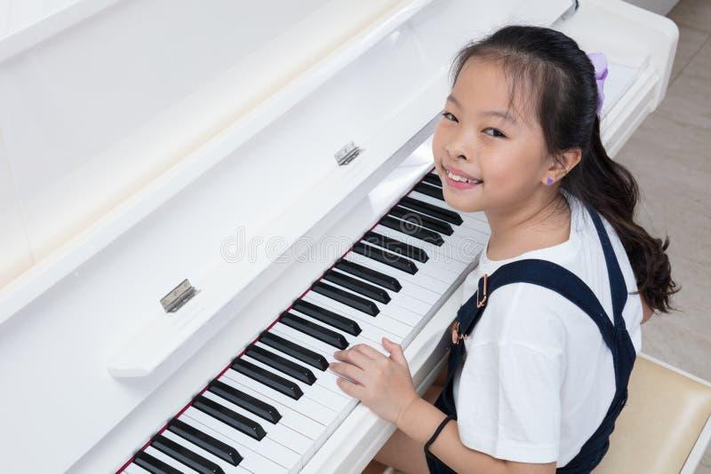 Menina chinesa asiática feliz que joga o piano clássico em casa imagens de stock