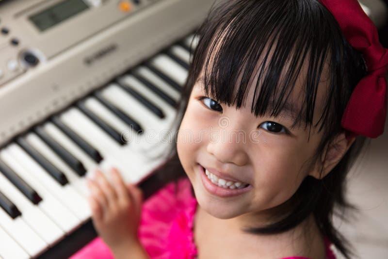 Menina chinesa asiática feliz que joga o teclado de piano bonde fotografia de stock