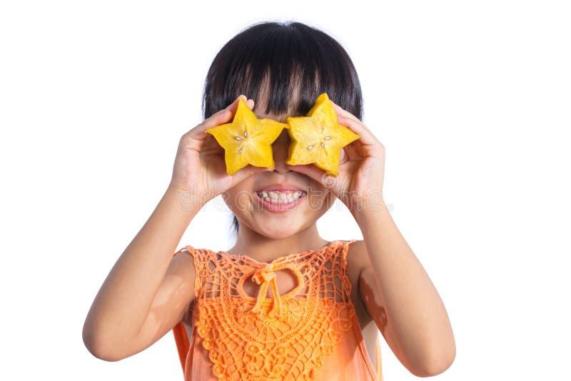 Menina chinesa asiática feliz que usa o starfruit como vidros imagens de stock