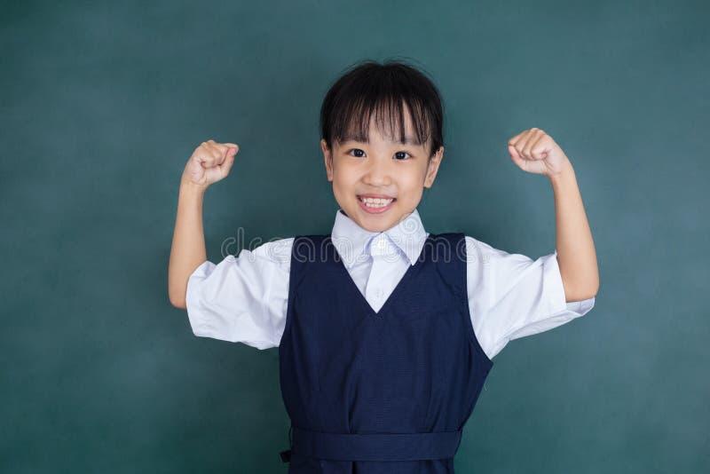 Menina chinesa asiática na posição uniforme com braços acima fotos de stock royalty free
