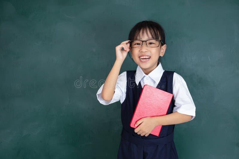 Menina chinesa asiática na posição uniforme contra o blac verde foto de stock royalty free