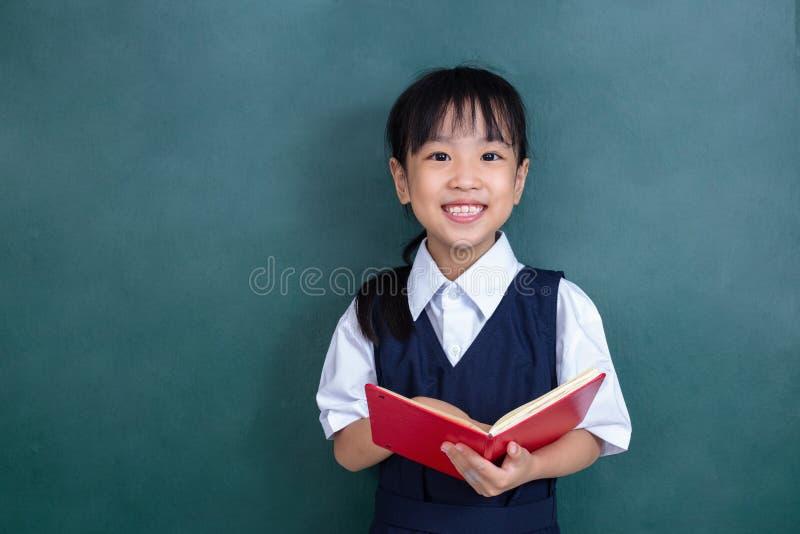 Menina chinesa asiática no livro de leitura uniforme contra o verde foto de stock