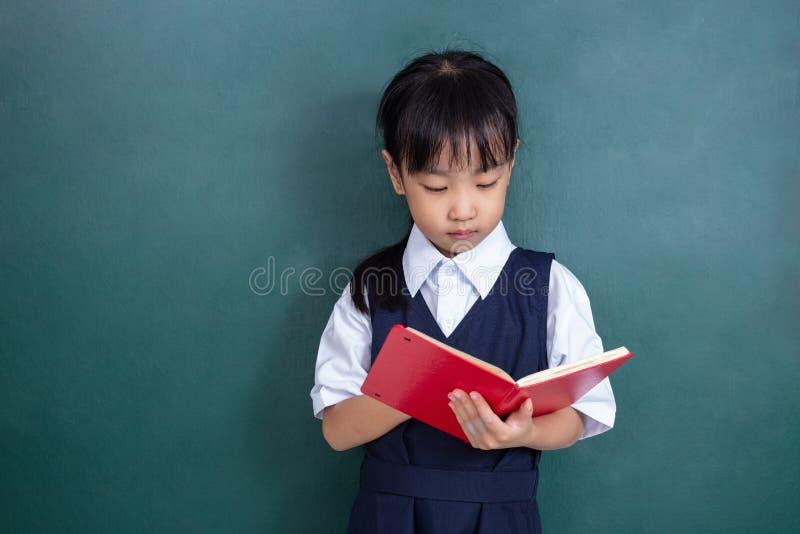 Menina chinesa asiática no livro de leitura uniforme contra o verde imagem de stock royalty free