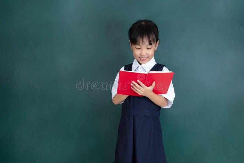 Menina chinesa asiática no livro de leitura uniforme contra o verde fotos de stock