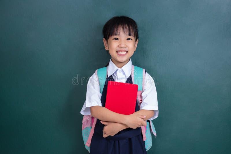 Menina chinesa asiática no saco de escola levando uniforme e para vaiar imagem de stock