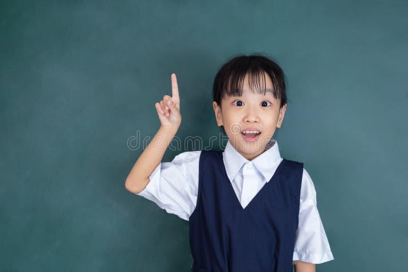 Menina chinesa asiática no uniforme que aponta o dedo acima foto de stock