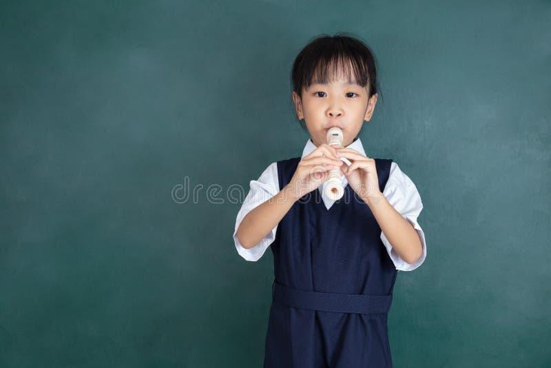 Menina chinesa asiática no uniforme que joga a flauta fotos de stock
