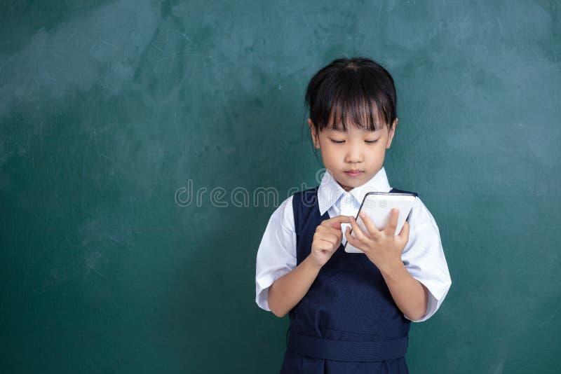 Menina chinesa asiática no uniforme que joga o agai digital da tabuleta imagens de stock
