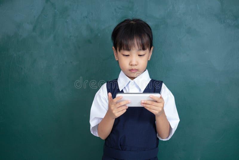 Menina chinesa asiática no uniforme que joga o agai digital da tabuleta imagem de stock royalty free
