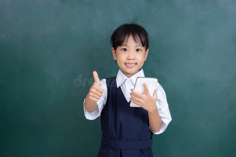 Menina chinesa asiática no uniforme que joga o agai digital da tabuleta fotografia de stock