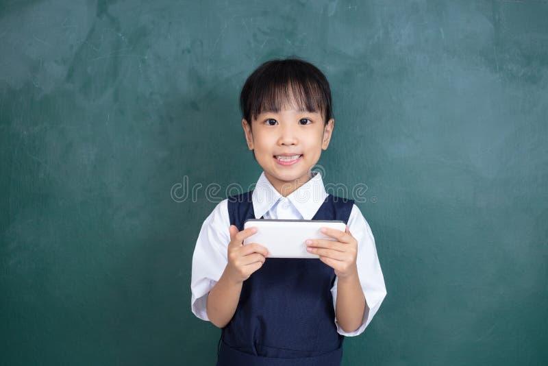 Menina chinesa asiática no uniforme que joga o agai digital da tabuleta fotos de stock