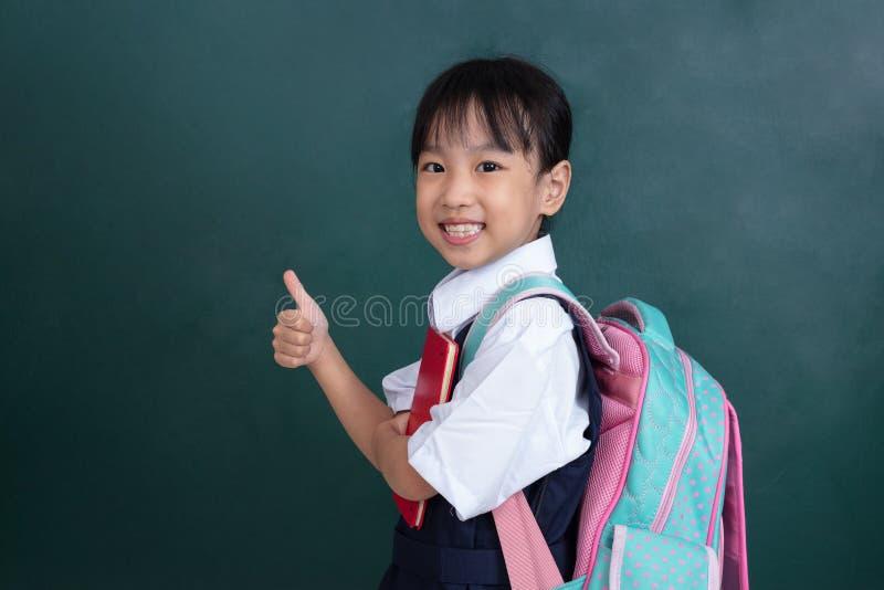 Menina chinesa asiática no uniforme que mostra os polegares acima contra g foto de stock