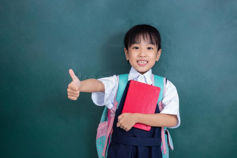 Menina chinesa asiática no uniforme que mostra os polegares acima contra g foto de stock royalty free