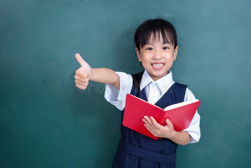 Menina chinesa asiática no uniforme que mostra os polegares acima contra g fotografia de stock royalty free